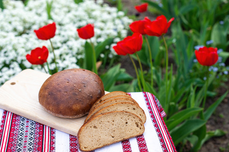 Rye bread on a wooden board against the background of spring flowers. fresh bread on a background of blooming tulips 版權商用圖片