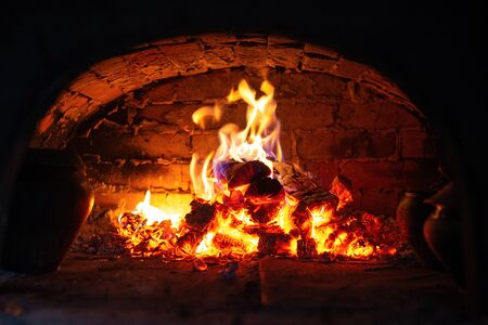 Village stove firewood and fire. Burning wood inside traditional oven Imagens - 147012859