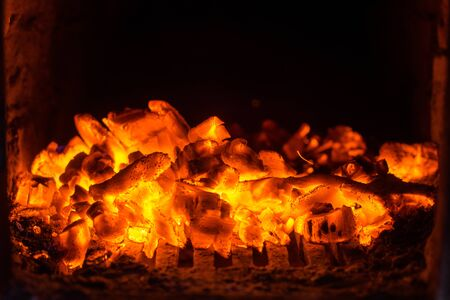 Red ember on black background. Hot red embers background Imagens