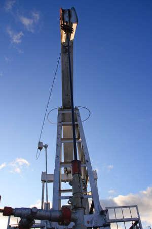 spiraglio: Una pompa olio estratto olio su uno sfondo di cielo blu Archivio Fotografico