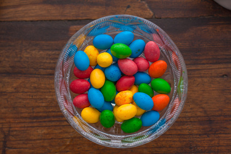chocolate eggs: Colorful chocolate eggs over a wooden table Stock Photo