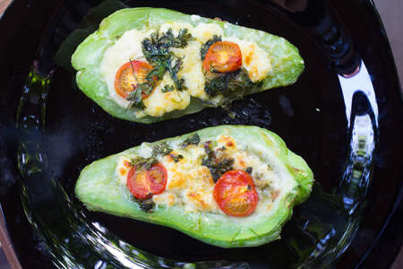 chayote: Chayote Stuffed  with cheese, cherry tomatoes and herbs Stock Photo