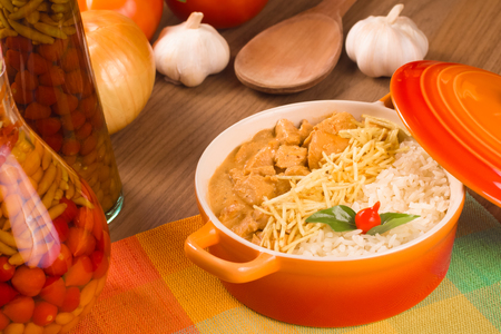 Stroganoff Chicken with rice over a wooden table Archivio Fotografico