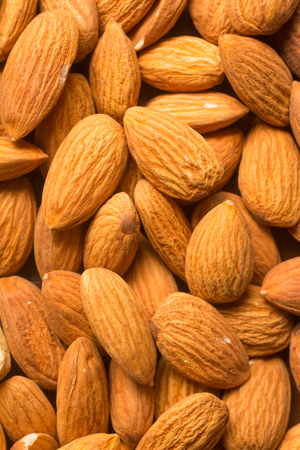 Close-Up on Almonds Nuts over a wooden table Stock Photo