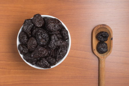 prunes: Prunes into a bowl over a wooden table Stock Photo