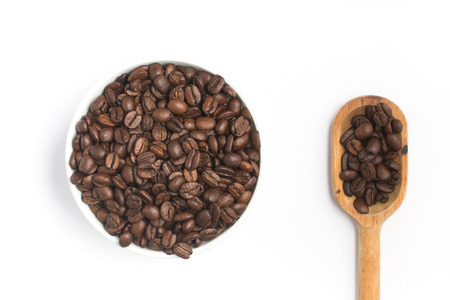 coffea: Coffee beans into a bowl and spoon on white background. Coffea arabica