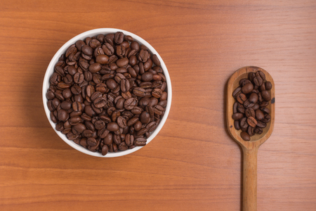 coffea: Coffee beans into a bowl and spoon over a wooden table. Coffea arabica Stock Photo