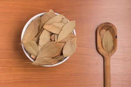 nobilis: Bulk Bay Leaves into a bowl over a wooden table. (Laurus nobilis)