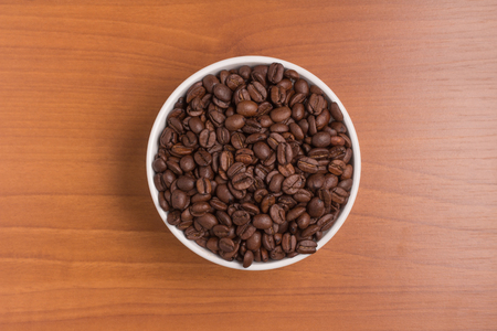 coffea: Coffee beans into a bowl over a wooden table. Coffea arabica Stock Photo