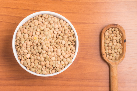 Lentils into a bowl and spoon over a wooden table. Stock Photo