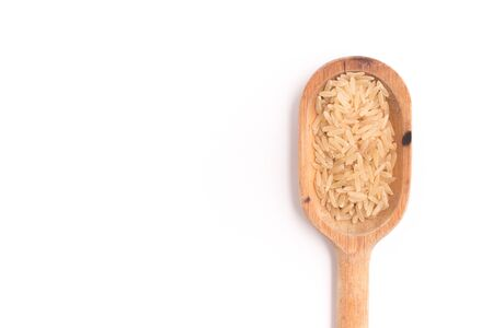 Raw Brown Rice into a spoon Stock Photo