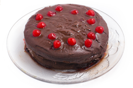 Homemade Chocolate Cake with cherry over a plate in white background