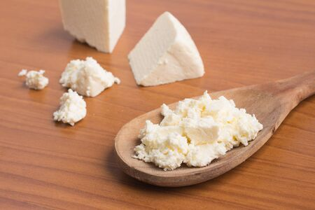 ricotta cheese: Ricotta Cheese into a spoon over a woooden table