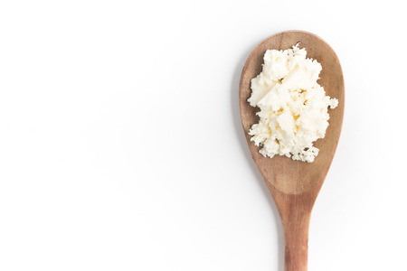 Ricotta Cheese into a spoon in white background