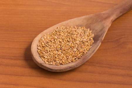 gold flax: Gold linseed into a spoon over a wooden table
