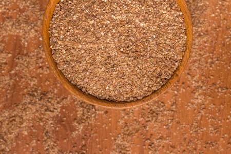 Ground Wheat into a bowl over a wooden table. Banco de Imagens