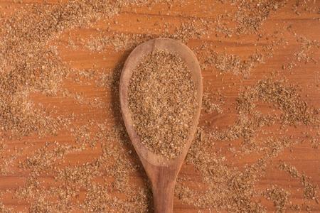 Ground Wheat into a spoon over a wooden table. Banco de Imagens