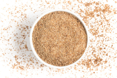 Ground Wheat into a bowl isolated in white background. Banco de Imagens