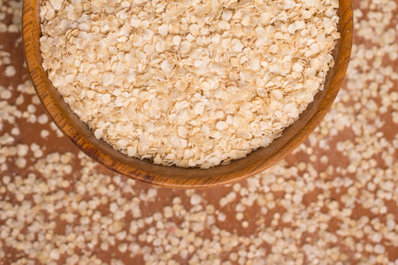 free dish: Quinoa Flakes into a bowl over a wooden table.