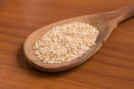 free dish: Quinoa Flakes into a spoon over a wooden table.