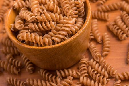 fusilli: Wholemeal Fusilli into a bowl over a wooden table