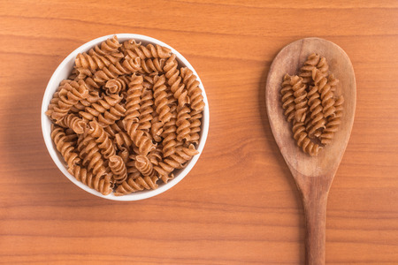 Wholemeal Fusilli into a bowl over a wooden table
