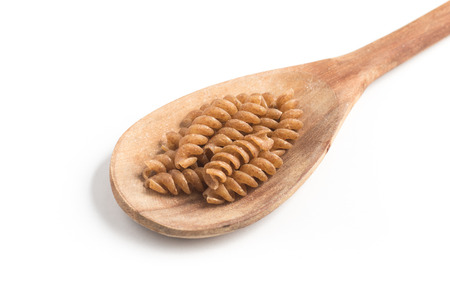 fusilli: Wholemeal Fusilli into a spoon isolated in white background