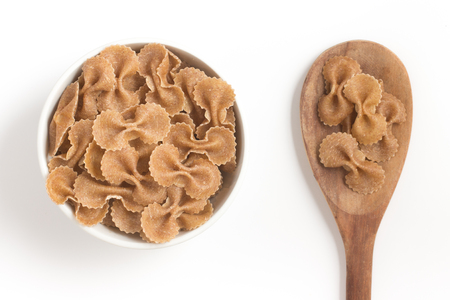 wholegrain: Wholegrain Farfalle into a bowl. wholemeal. Integral isolated in white background Stock Photo