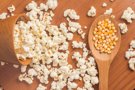 Popcorn into a bowl over a wooden table