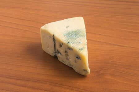 stilton: Slice of Gongonzola Cheese. Roquefort over a wooden table