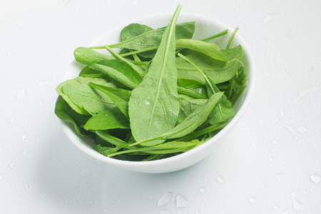 Arugula Leaves into a bowl over a white background