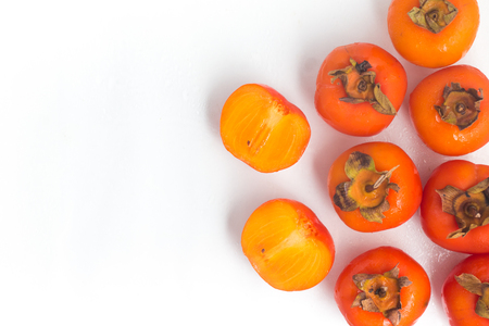 Fresh Persimmon fruit frame over a wet white background