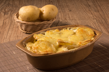 Gratin potatoes in rustic dish over a wooden table