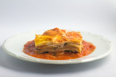 Vegetarian Lasagna with eggplant and spinach over a plate on white background