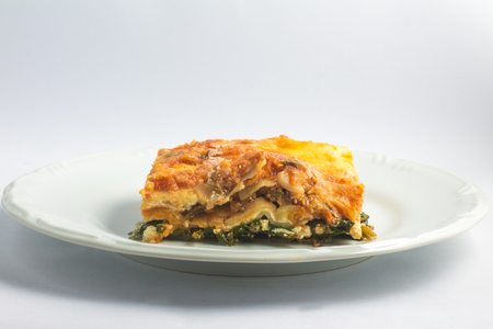 Vegetarische Lasagna's met aubergine en spinazie over een plaat op witte achtergrond