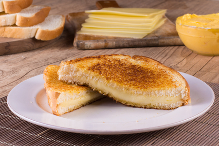 Hot cheese with toasted bread over a wooden table