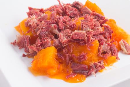 Brazilian Jaba com Jerimum. Jerked beef or Dry Meet with Pumpkin on white background Stock Photo