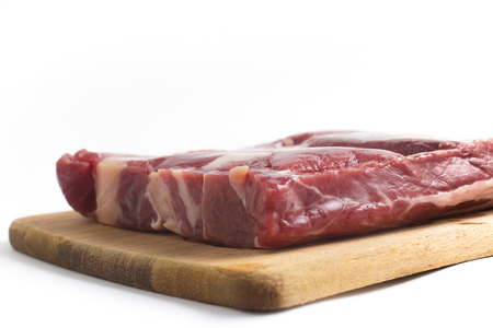 Jerked Beef. Brazilian Carne seca on a wooden board isolated on white background Stock Photo