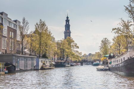 AMSTERDAM, NETHERLANDS - APRIL 14, 2019: Munttoren clock tower, Houses and Boats on Amsterdam Canal, Netherlands.