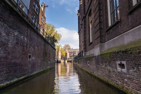 AMSTERDAM, NETHERLANDS - APRIL 14, 2019: Houses and Boats on Amsterdam Canal, Netherlands. 報道画像