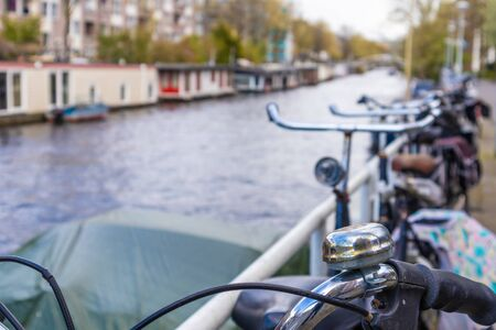 AMSTERDAM, NETHERLANDS - APRIL 13, 2019: Bicycles lining a bridge over the canals of Amsterdam, Netherlands. Close-up Photo 報道画像