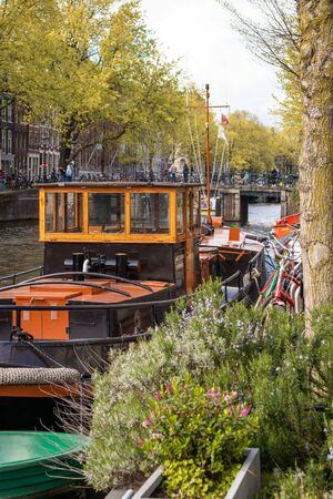 AMSTERDAM, NETHERLANDS - APRIL 13, 2019: Houses and Boats on Amsterdam Canal, Netherlands.