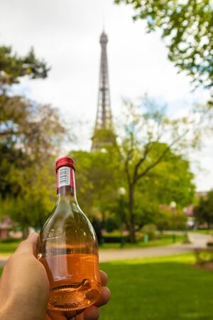 Paris, France - APRIL 9, 2019: Eifel tower seen from a different angle. Hand holding a bottle of wine, Paris, France