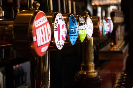 London, England - APRIL 1, 2019: Draught beer taps in a traditional pub in London, UK 報道画像