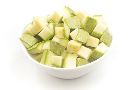 Zucchini Diced. Cut into cubes in a bowl on white background Фото со стока
