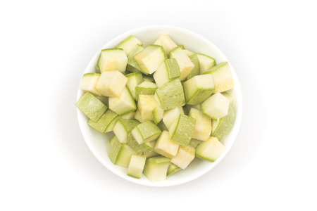 Zucchini Diced. Cut into cubes in a bowl on white background. Top view Фото со стока