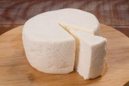 Slice of Ricotta Cheese over a wooden board and table Archivio Fotografico - 125392961