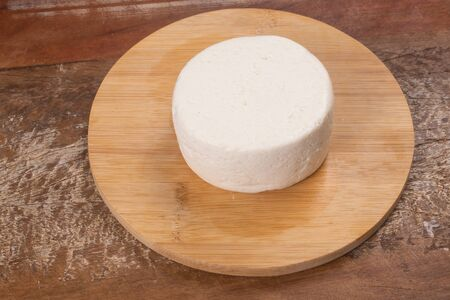 Ricotta Cheese over a wooden board and table Archivio Fotografico - 125393408