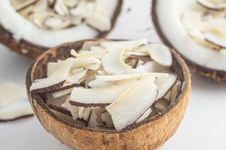 Shaved Coconut into a coconut bowl over white background