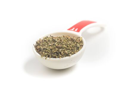 Dried Oregano into a Tablespoon on white background